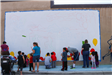 People Stand in Front of Outlined Mural