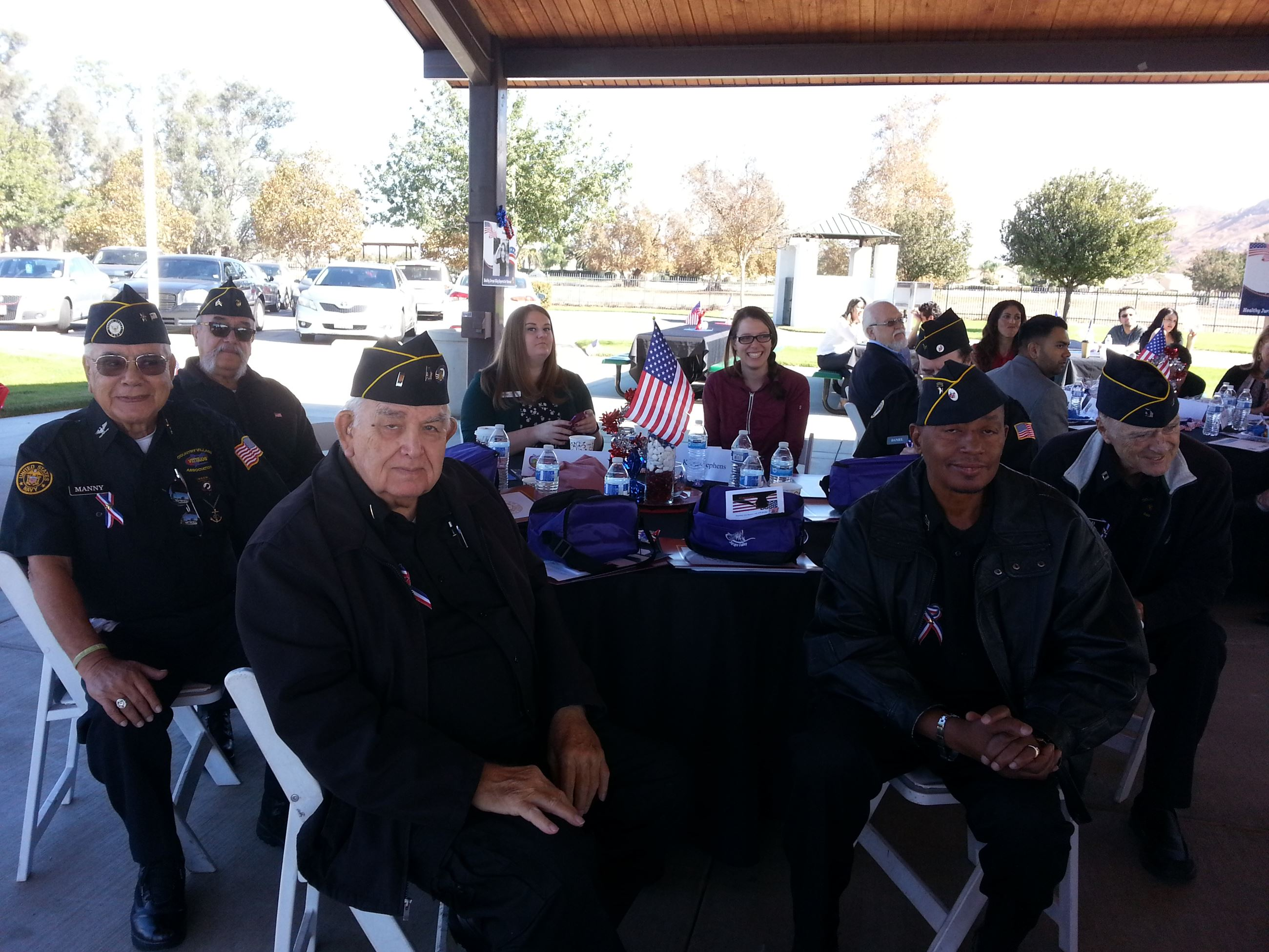 Group of Elderly Veterans Sitting at Table Together at Celebrating Veterans Event